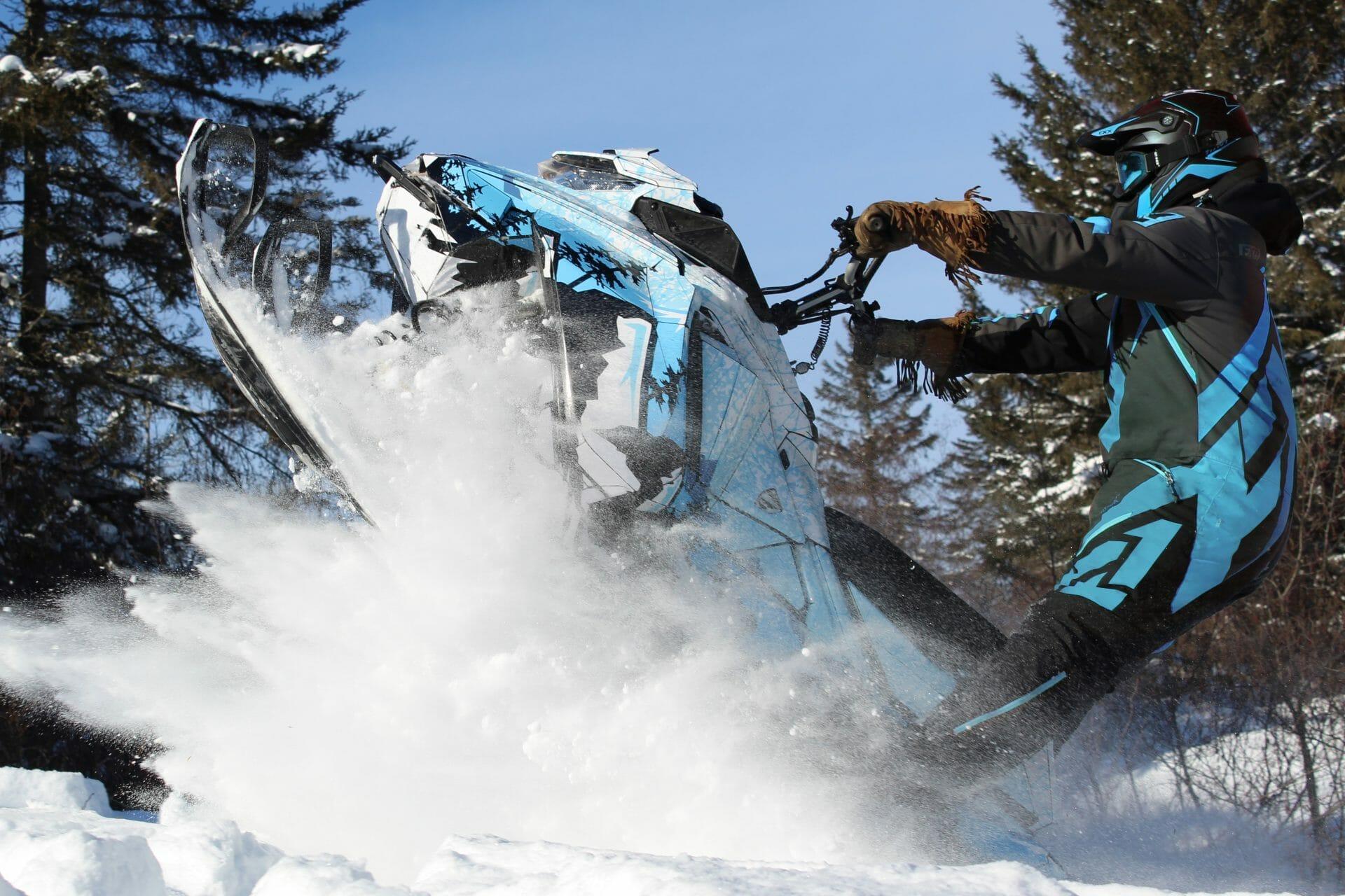 Motoneigiste en action avec sa motoneige et un design de kit graphique bleu